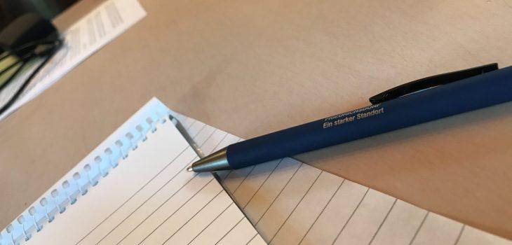 Block und Stift auf Tisch